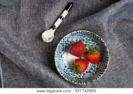 Fresh Strawberry In Ceramic Bowl On Gray Dish Cloth