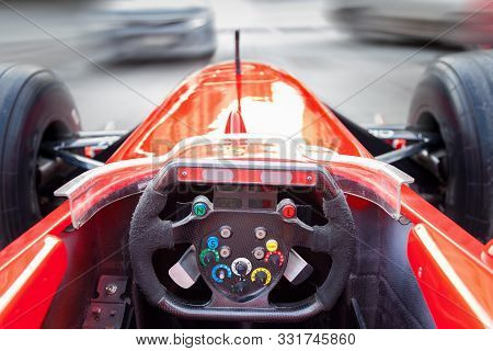 A Driver Driving A Red Formula 1 Sports Car During A City Race At High Speed In Traffic Jams On The