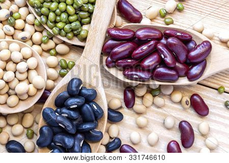Many Types Of Beans Are Separated In A Spoon On A Wood Table Such As Mung Bean, Soybean, Black Bean,