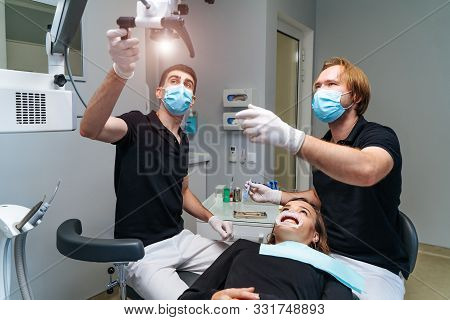Male Dentists With Dental Tools - Microscope, Mirror And Probe Checking Up Patients Teeth At Modern