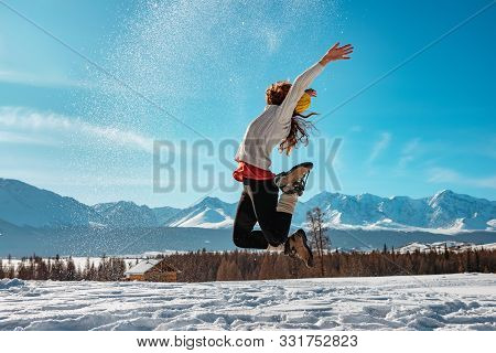 Happy Girl Jumps With Snow Against Snowcapped Mountains. Winter Concept