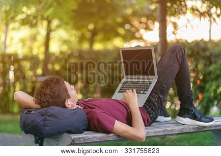 Smiling teenage boy with a laptop in the park. Handsome young man works on a notebook, outdoors. Cheerful guy holds a laptop on the knees and looking to the screen. Teenager in headphones with laptop
