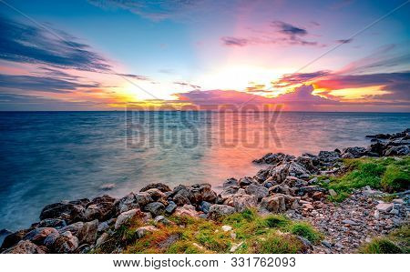 Rocks On Stone Beach At Sunset. Beautiful Landscape Of Calm Sea. Tropical Sea At Dusk. Dramatic Colo
