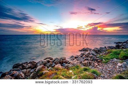 Rocks On Stone Beach At Sunset. Beautiful Landscape Of Calm Sea. Tropical Sea At Dusk. Dramatic Colo