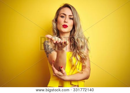 Young attactive woman wearing t-shirt standing over yellow isolated background looking at the camera blowing a kiss with hand on air being lovely and sexy. Love expression.