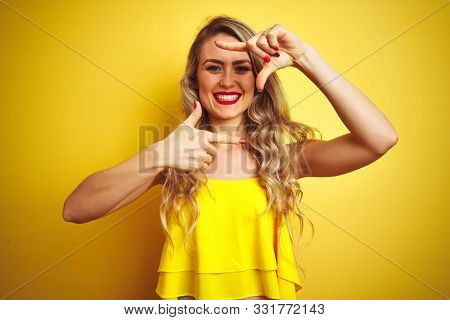 Young attactive woman wearing t-shirt standing over yellow isolated background smiling making frame with hands and fingers with happy face. Creativity and photography concept.