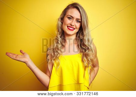 Young attactive woman wearing t-shirt standing over yellow isolated background smiling cheerful presenting and pointing with palm of hand looking at the camera.