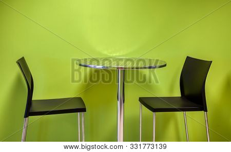 Standard metallic round table and chairs with black plastic backrest on green background