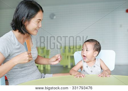 Little Asian Baby Boy And Mother Playing Flash Card For Right Brain Development At The Playroom. Foc