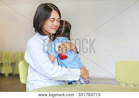 Asian Mom Hugging Daughter On Mother's Day In Thailand. Little Girl Pay Respect And Give Thai Tradit