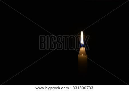 Candle Burning In The Black Background. Located On The Right Side Of The Shot.