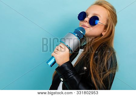 Photo Of A Teenage Girl In Blue Sunglasses Against A Blue Wall, A Girl With A Microphone In A Rocker
