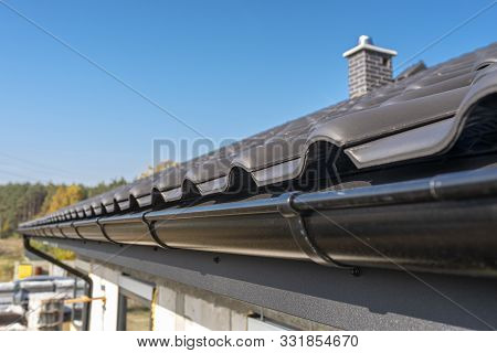 A Metal, Black Gutter On A Roof Covered With Ceramic Tiles. Close Up Shot.