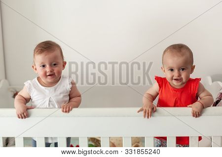 Happy Fraternal Twins Sisters Having Fun, Standing In Crib. Happy Baby. Baby Emotions. Baby Smile.