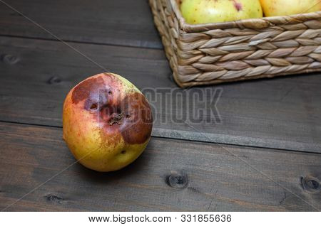 Ugly Apples At Wicker Basket On The Wooden Brown Background. Close Up.
