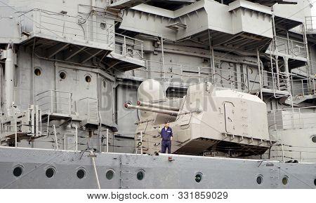 Novorossiysk, Russia - May, 2014: Sailor and ship's gun. The cruiser Mikhail Kutuzov. Ship Museum.