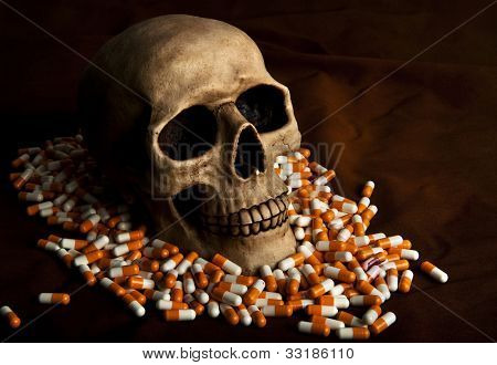 Dramatic skull in the pile of drugs symbolises sickness and danger of abuse