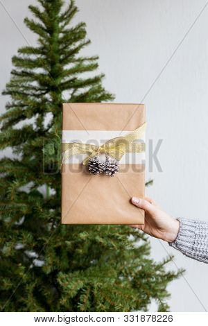 Gift In Hand With Christmas Tree At Background. Concept Of Present Sales