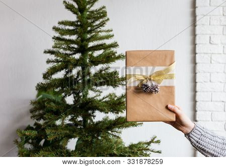 Gift Box In Woman's Hand And Christmas Tree Behind