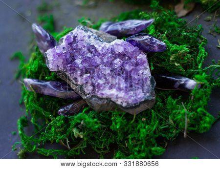 Purple Amethyst Gemstonea And Geode On Bright Green Moss