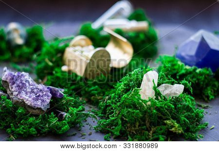 Amethyst Geode, Golden Chest And Quartz Crystal On Bright Green Moss