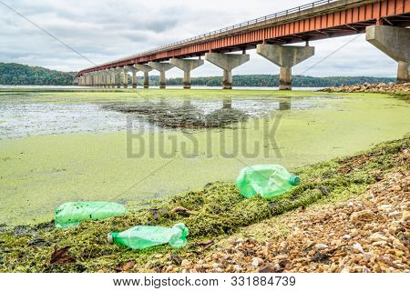 plastic bottle trash on river shore - Tennessee River with John Coffee Memorial Bridge (Natchez Trace National Parkway)