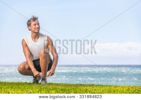 Happy healthy man getting ready to walk or jog on summer beach - Active lifestyle for weight loss runner going running outside.