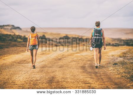 Hiking people walking on desert trail hike path with backpacks on mountain landscape nature. Hikers travel adventure wanderlust summer vacation.
