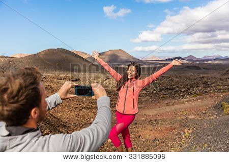 Tourists taking picture vlogging outside on Europe travel, girl posing for boyfriend with arms up having fun on Timanfaya National Park, Lanzarote, Canary Islands.