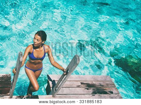 Luxury resort bikini woman swimming coming out of water after swim on overwater bungalow terrace at high end hotel. Sexy Asian girl in swimwear with tanned body.
