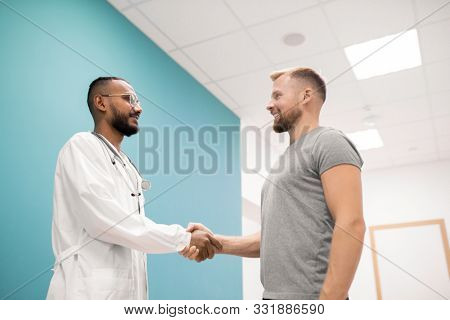 Young successful clinician in whitecoat and his patient shaking hands in hospital after finishing of medical treatment