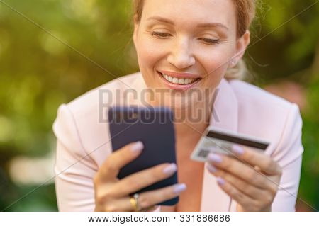 Businesswoman with a credit card and phone makes purchasing outdoors. Successful  woman is using smart phone and bank card for online shopping. Beautiful smiling white woman holds card and cell phone
