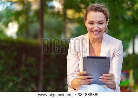 Smiling businesswoman with a tablet in the park. Successful  businesswoman is using tablet, outdoors. Adult woman communicating with a people uses tablet. Woman has a video call on gadget.