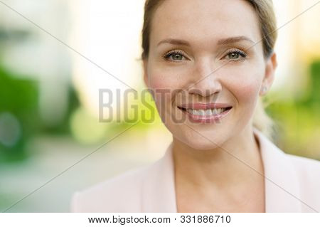 Close-up portrait of a smiling woman on the street. Happy woman's face closeup, outdoors. Happy businesswoman in a light jacket looks at the camera. Urban portrait of a beautiful blonde woman.