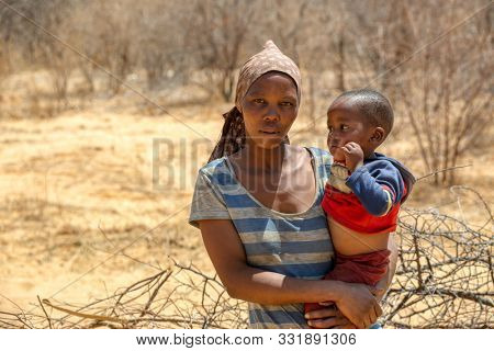African woman with a child in a village in  Botswana standing in front of  the bush in Kalahari , Botswana