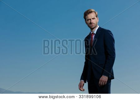 Bothered young businessman looking away and frowning while wearing a blue suit, standing on outdoor sky background