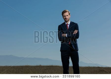 Bothered businessman holding his hands crossed at his chest while wearing a blue suit, standing on outdoor mountains and field background