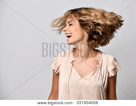 Young Woman In A Beige Short-sleeved Satin Blouse Shakes Her Head With Her Hair. The Concept Of Joy,