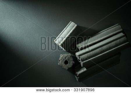 Carbon activated. Bamboo charcoal compressed in to stick on darkness background. Has the ability to absorb toxins in the human body. Concept of health care. Top view and copy space. poster