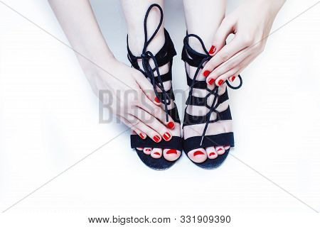 fashion concept people: woman with red nails manicure pedicure tying shoelaces on hight heel shoes isolated on white background close up stylish poster