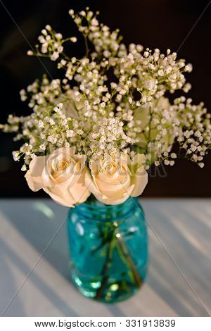 Bouquet Of White Roses And Babies Breath In A Glass Vase On A White Tablecloth, At A Wedding Recepti