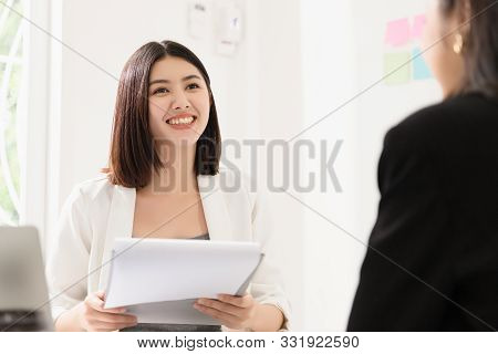 A Young Attractive Asian Woman Is Interviewing For A Job. Her Interviewers Are Diverse. Human Resour