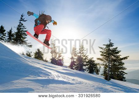 Snowboarder Jumping on the Red Snowboard in the Mountains at Sunny Day. Snowboarding and Winter Sports