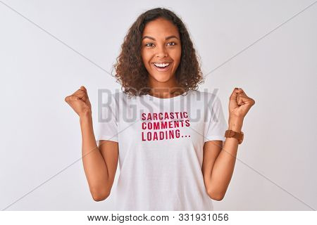 Brazilian woman wearing fanny t-shirt with irony comments over isolated white background screaming proud and celebrating victory and success very excited, cheering emotion