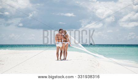 Newlyweds in white bikinis on a desert island