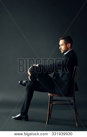Confident Handsome Man In Black Suit Sitting On The Chair On Dark Backround. Profile View Full Lengh
