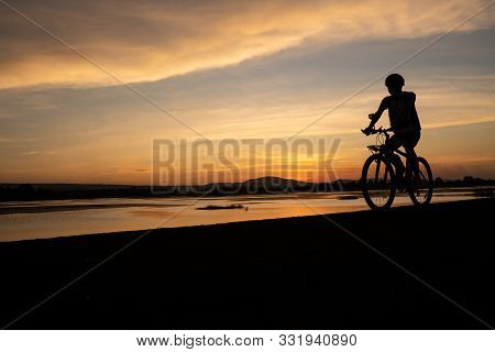 Asian Men Cycling Bicycle On The Road In The Sunset Time