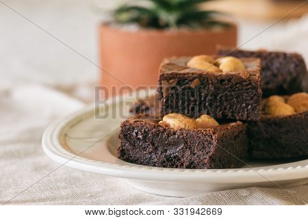 Fresh Baked Dark Chocolate Fudge Brownies. Sweet Brownie Topping With Cashew Nut Stacked On White Pl