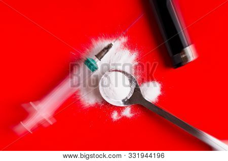 Syringe And Narcotic Powder On A Red Background.hard Drugs Top View. Tools Of A Heroin Addict. Spoon