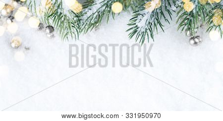 Christmas And New Year Snowy Background. Green Twigs Border.